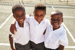 Young African schoolboys smiling to camera in a playground