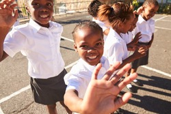 Young African schoolgirls in a playground waving to camera