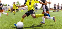 Young african soccer player running fast and kicking white football ball. Youth footballers compete in tournament match. Soccer athlete kicking ball. School sports competition