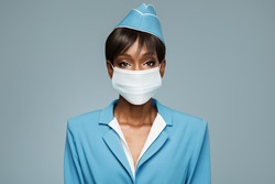Young african stewardess wearing an antiviral mask on her face. Blue background.