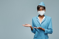 Young african stewardess wearing an antiviral mask on her face. Boarding gesture.