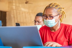 young african students in a classroom, one using a laptop, both wearing face masks