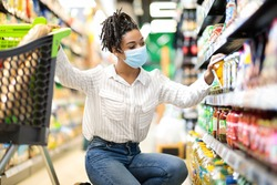 Young African Woman Doing Grocery Shopping Taking Food Product From Shelf In Supermarket Store Aisle, Wearing Protective Face Mask. Lady Customer Buying Groceries Essentials And Supplies Concept