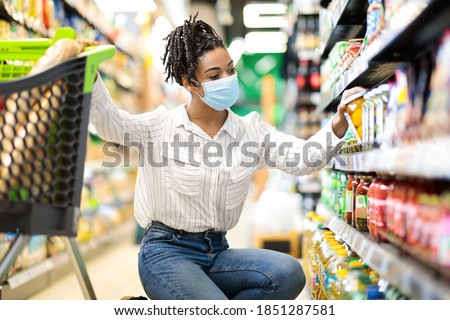 Young African Woman Doing Grocery Shopping Taking Food Product From Shelf In Supermarket Store Aisle, Wearing Protective Face Mask. Lady Customer Buying Groceries Essentials And Supplies Concept Stockfoto ©