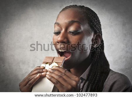 Young african woman eating a chocolate bar