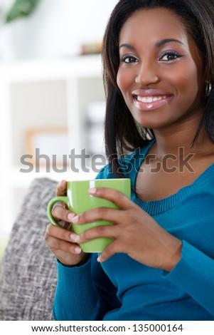 Young African woman enjoying in coffee or tea