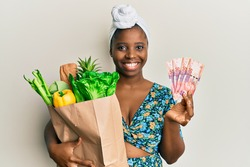 Young african woman holding groceries and 50 rand banknotes smiling with a happy and cool smile on face. showing teeth.