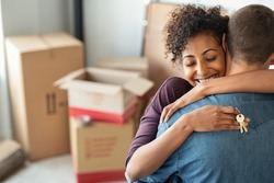 Young african woman holding home keys while hugging boyfriend in their new apartment after buying real estate. Lovely girl holding keys from new home and embracing man. Couple around cardboard boxes.