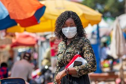 Young African woman in the local market after lockdown holding phone and purse - millennial wearing face mask for protection during corona virus pandemic - concept on local market shopping