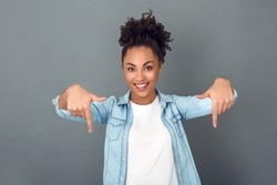 Young african woman isolated on grey wall studio casual daily lifestyle pointing down