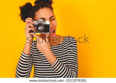Young african woman isolated on yellow wall studio teen style taking pictures close-up
