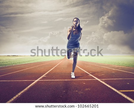 Young african woman running on a running track