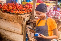 young african woman selling in a local african market holding a mobile point of sale system and using her mobile phone