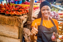 young african woman selling tomatoes in a local african market smiling an giving thumbs up gesture