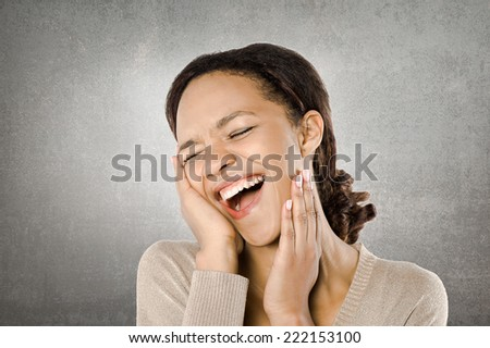 Young African woman smiling holding hands near her face #222153100