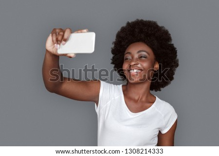 Young african woman standing isolated on gray wall taking selfie pictures on smartphone looking camera laughing cheerful