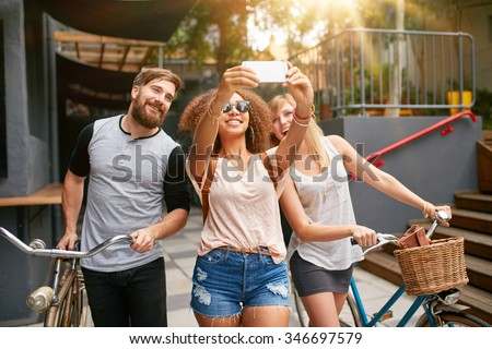 Young african woman taking a self portrait with her friends. African woman taking selfie with mobile phone. Young friends with bikes having fun on city street.