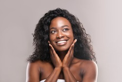 Young african woman touching her smooth cheeks, applying moisturizer cream on her pretty face, grey studio background