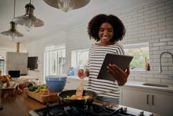 Young african woman watching recipe in digital tablet while cooking lunch in modern kitchen