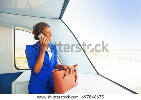 young African woman  wearing formals  talking on phone while traveling in a train  #697846675