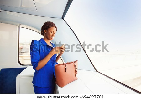 young African woman  wearing formals  using her phone while traveling in a train #694697701