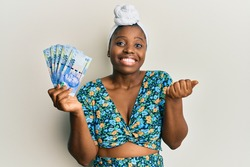 Young african woman wearing hair turban holding south african 100 rand banknotes screaming proud, celebrating victory and success very excited with raised arm