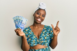 Young african woman wearing hair turban holding south african 100 rand banknotes smiling happy pointing with hand and finger to the side