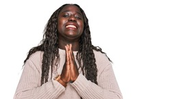 Young african woman wearing wool winter sweater begging and praying with hands together with hope expression on face very emotional and worried. begging.