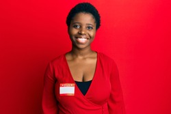 Young african woman with short hair wearing hello my name is sticker identification looking positive and happy standing and smiling with a confident smile showing teeth