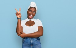 Young african woman with turban wearing hair turban over isolated background smiling with happy face winking at the camera doing victory sign with fingers. number two.