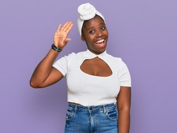 Young african woman with turban wearing hair turban over isolated background waiving saying hello happy and smiling, friendly welcome gesture