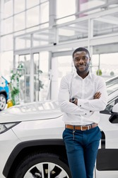 young africanamerican man came to see automobiles in dealership or cars showroom, he stands next to business class auto