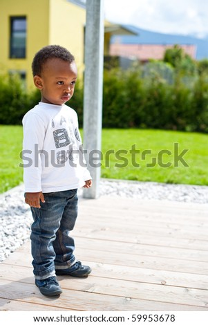Young afro american baby playing around in the garden.
