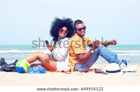 Young afro american couple having fun back to back at the beach using mobile phone - Attractive african models holding smartphone joyful summer moments sitting by ocean - Vintage filter modified ball