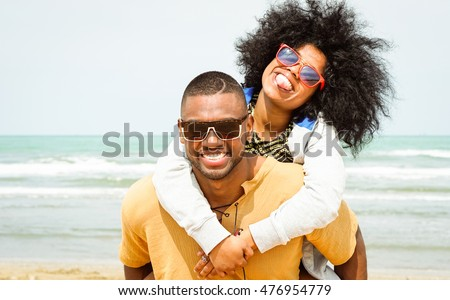Young afro american couple playing piggyback ride on beach - Cheerful african friends having fun at day with blue ocean background - Concept of lovers happy moments on summer holiday - Vintage filter #476954779