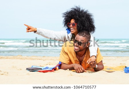 Young afro american couple  pointing finger relaxing on beach - Cheerful african friends having fun at day on blue ocean background - Concept of lovers happy moments on summer holiday - Vintage filter #1064710577