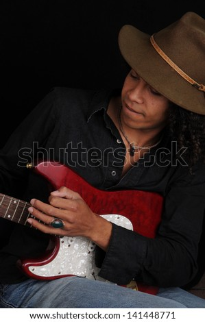 Young Afro American Guitar Player/Serious Guitar Player/Young man demonstrates his guitar skills as a musician.