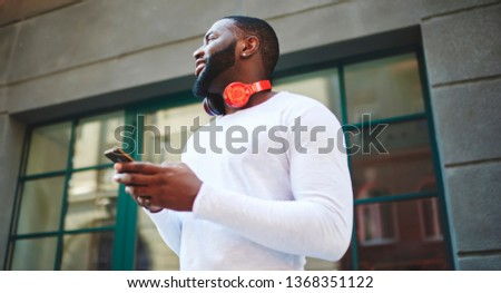 Young afro american man in trendy outfit standing on urban setting and looking away, dark skinned hipster guy with bluetooth electronic headphones on neck using smartphone gadget on publicity area