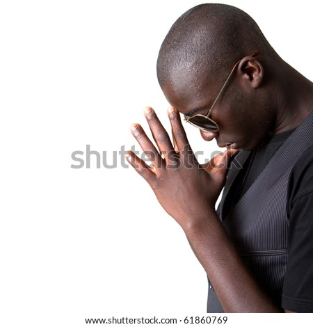 Young afro american teenager praying with sunglasses and a stylish suit.