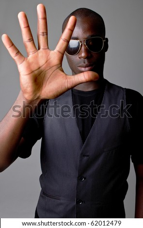 Young afro american teenager showing a stop sign with his hand.