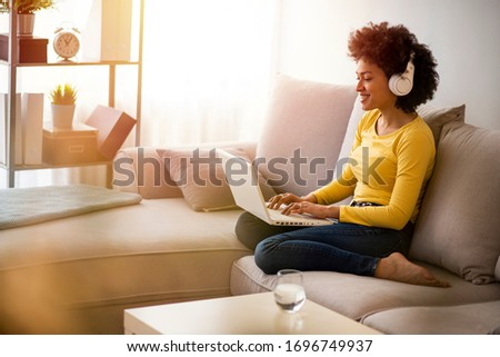Young afro-american Woman drinking water and surfing the net on the sofa at home. Young woman working from home office. Freelancer using laptop, phone and the Internet. Workplace in living room