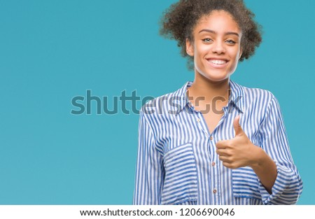 Young afro american woman over isolated background doing happy thumbs up gesture with hand. Approving expression looking at the camera with showing success. #1206690046