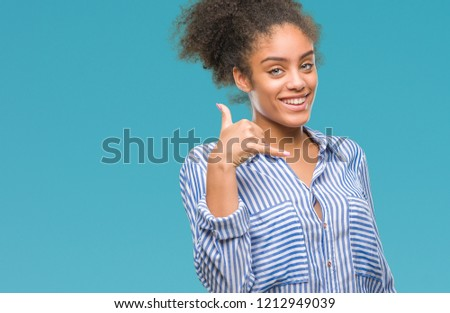 Young afro american woman over isolated background smiling doing phone gesture with hand and fingers like talking on the telephone. Communicating concepts. #1212949039