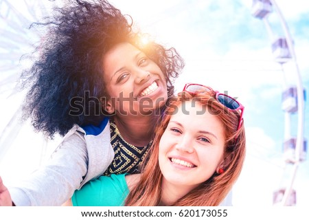 Young afro american woman playing piggyback ride with girlfriend - Cheerful  interracial   couple of girls having fun taking selfie outdoors - Concept of modern relations main focus on top left female