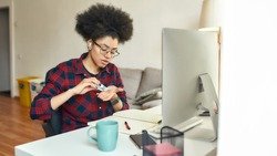 Young afro american woman using hand sanitizer, antiseptic gel while sitting at her workplace and working or studying online from home. Hygiene and Healthcare. Covid 19. Self isolation. Stay home