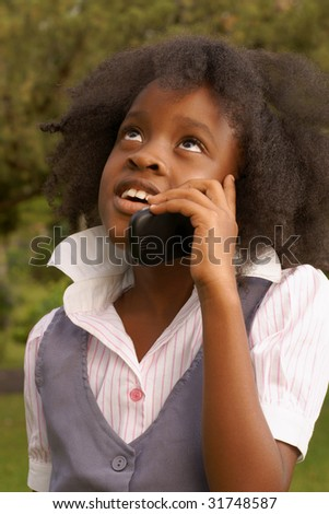 young afro caribbean girl talking on cell phone in park