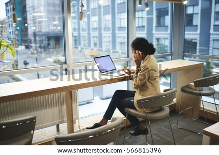 Young afroamerican executive making remote job being in business trip sitting at table in coworking space talking on the phone with entrepreneur using laptop computer with mock up screen with wifi stock photo