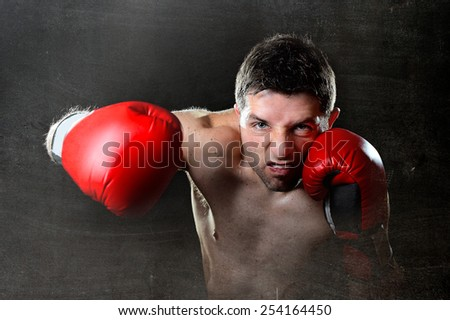 young aggressive fighter man training shadow boxing with red fighting gloves throwing vicious right hook punch in angry rage face expression isolated on black grunge dirty background