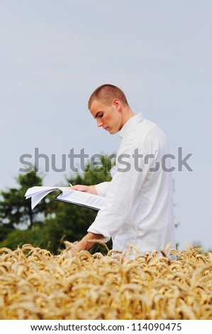 Young agronomist checking results of his experiment in the wheat field