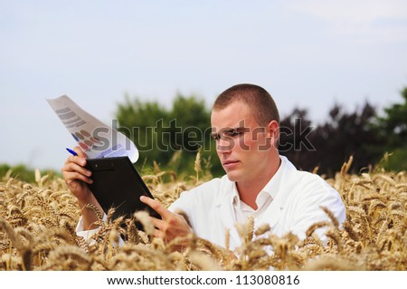 Young agronomist or a student checks results of his experiment in the wheat field
